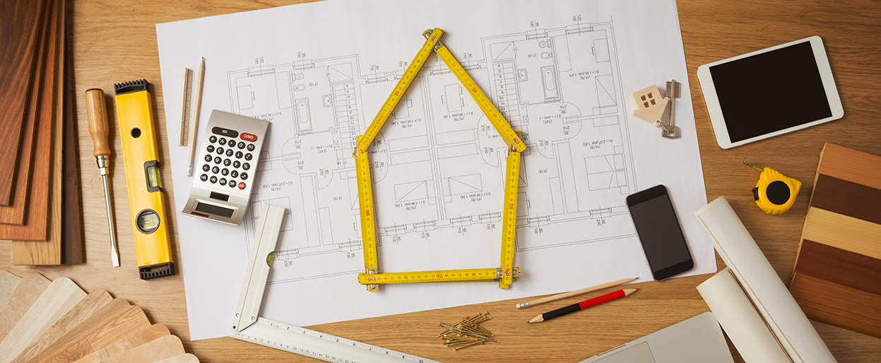 home design blueprints with a variety of design tools on top, including measuring tape in the shape of a house