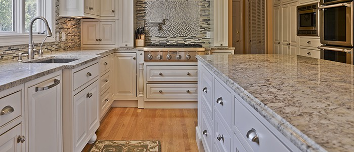 a kitchen remodel with brown granite countertops, white cabinets, and a range stove with tile backsplash and a pot filler