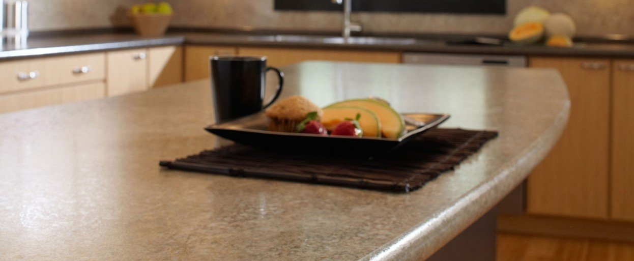 close up of a brown laminate kitchen countertop with a plate of food and a cup of coffee on top