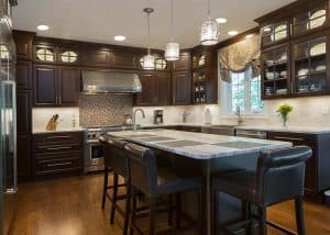 large dark finish kitchen with island and wall cabinets to the ceiling