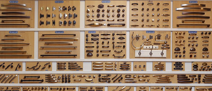 a wall of different cabinet hardware options in a Norfolk Kitchen & Bath showroom
