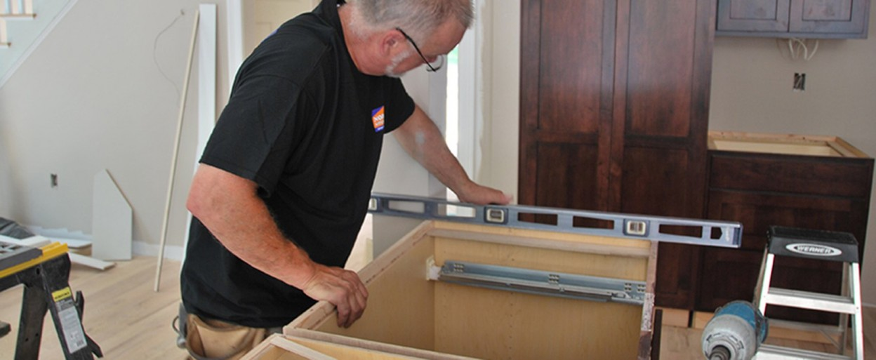 a Norfolk kitchen installer checking to make sure a base cabinet is level during install