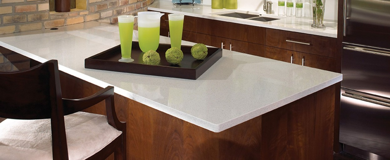a white stone countertop on brown stained cabinets