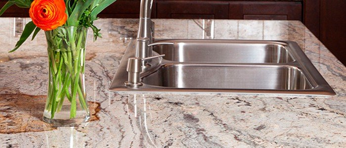 close up of a granite countertop and a stainless steel drop in sink with faucet