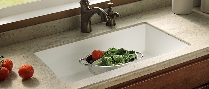 close up of a solid surface countertop with a large white sink and vegetables in a strainer