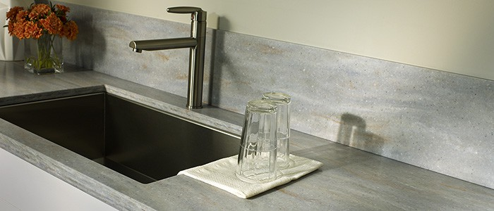 close up of a solid surface countertop with 2 glasses next to a stainless steel sink