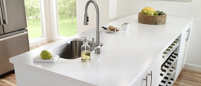 a kitchen island with a solid surface countertop and a stainless steel sink and faucet