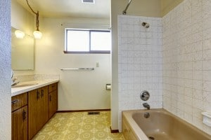 Outdated bathroom with linoleum tile and dark wood cabinets