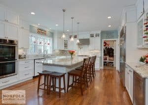 white kitchen with hardwood floors and dark wood stools at island