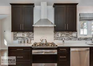 Dark maple kitchen showing quartz countertop up behind stove area and decorative tile everywhere else for backsplash