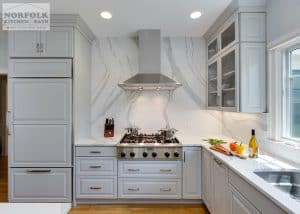 Light Grey kitchen with stainless cooktop and modern stainless hood, with white Cambria on wall up to ceiling