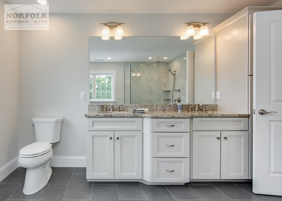 a double bathroom vanity with a granite vanity countertop next to a white toilet