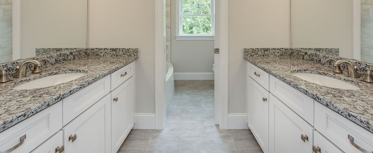 a jack and jill bathroom with 2 vanities with granite vanity countertops and an open doorway that leads to the shower/tub combo and toilet
