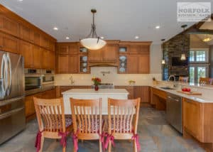 very large u shape wood kitchen with chairs at a table area facing kitchen at island