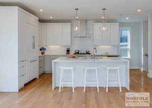 White kitchen design style with island and white stools and hardwood floors