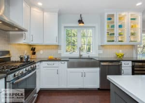 white kitchen featuring stainless appliances and cherry colored flooring and glass door cabinets