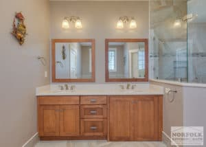 bathroom with wood cabinets and granite tops and mirrors