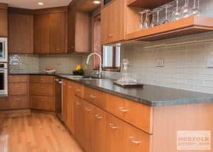 Medium toned slab door style cabinets with dark granite and hardwoood floors