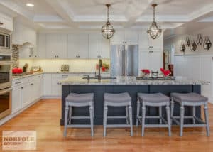 white kitchen with black island and grey stools.