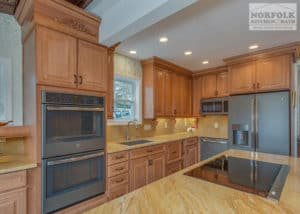 Maple Kitchen with yellow toned granite tops and large wall oven