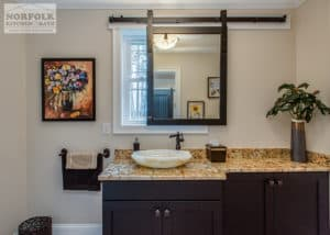 dark wood bath cabinets and granite with vessel sink on top and sliding barn door mirror