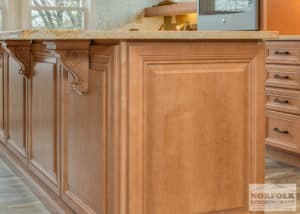 Lightly stained maple cabinet on island with decorative corbels to support island top