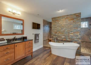 x large bath with wood cabinets and black granite and soaking tub with green small tiled wall