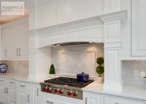 White cabinetry over a cooktop with lots of decorative molding