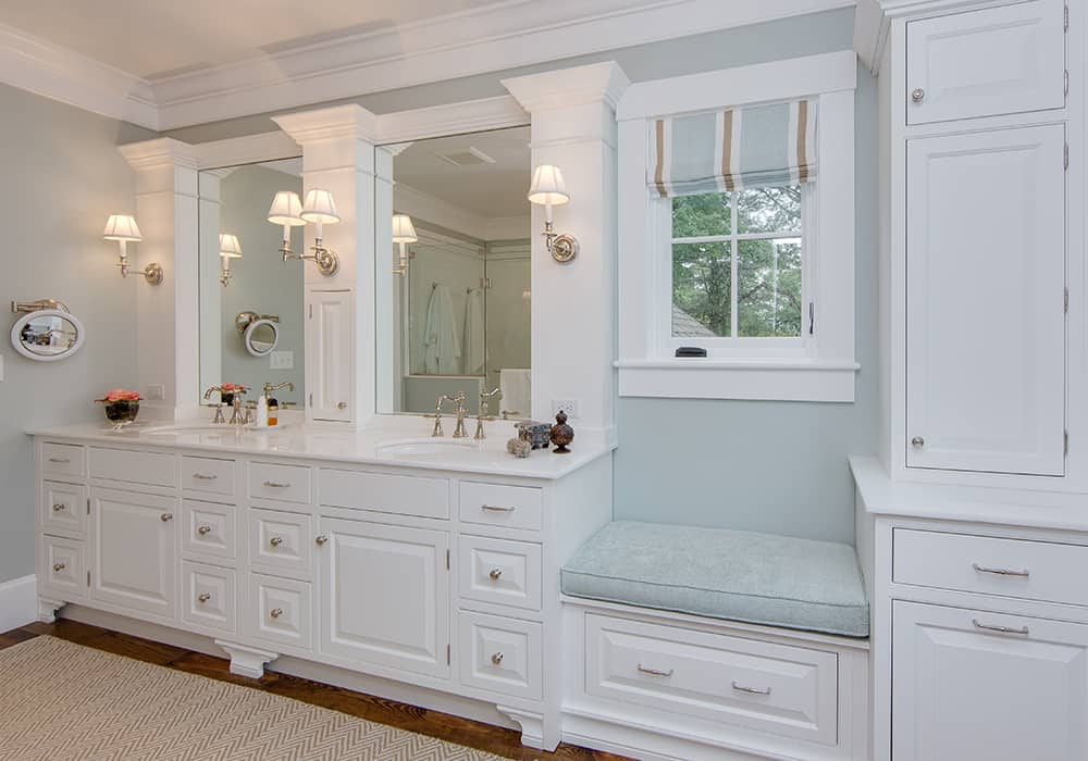 a custom bath vanity with white cabinets, dual sinks, and a window bench with cushion.