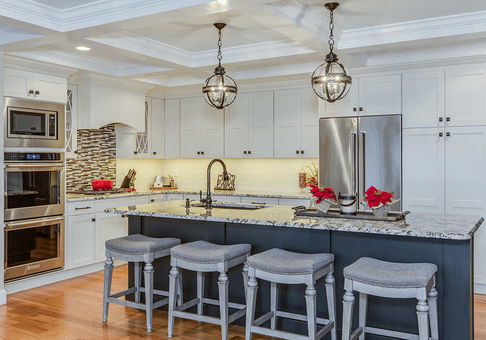 white custom kitchen cabinets and a dark stained island with 4 stools and pendant lighting