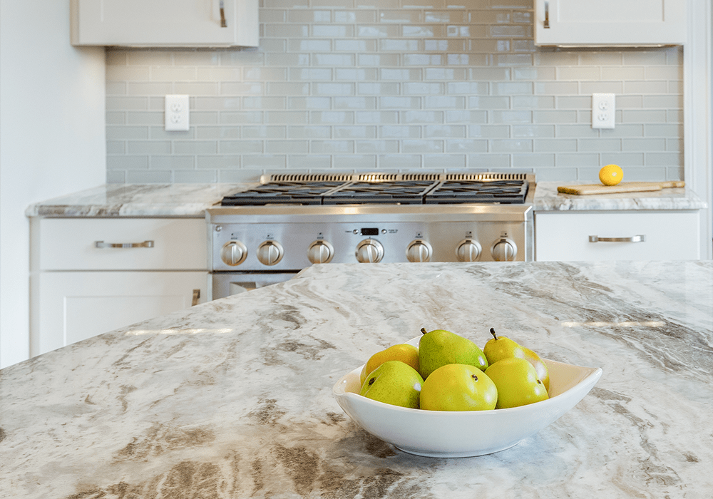 close up of a fantasy brown granite kitchen countertop with a bowl of green pears on top