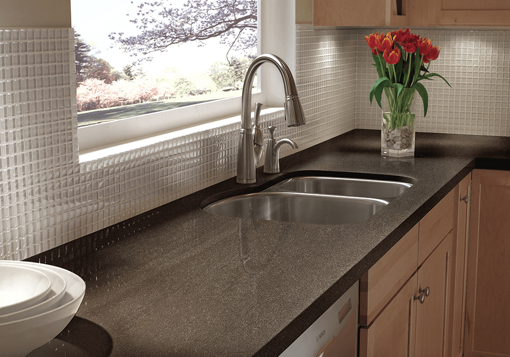 close up of a dark solid surface kitchen countertop with a stainless steel sink and a pull-down faucet