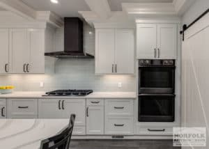 white kitchen cabinets with quartz countertops and black stainless steel appliances. Black stainless is an up and coming kitchen trend