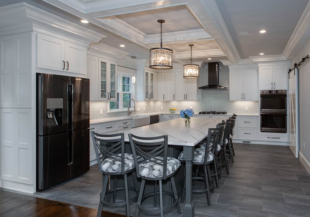 beautiful white kitchen with island and grey floors detailed tray ceiling