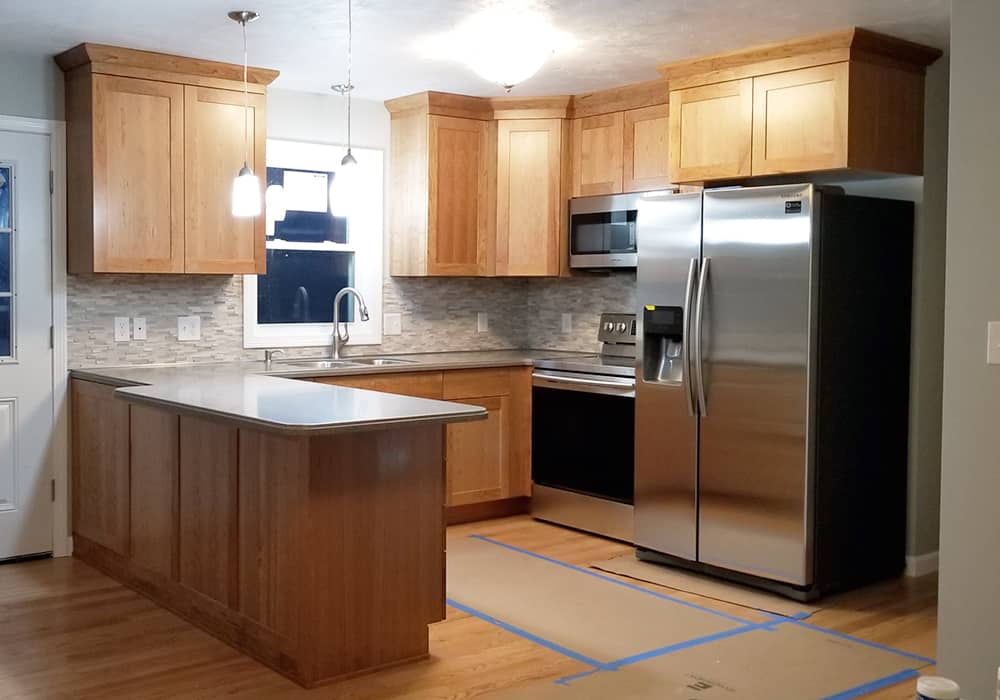 light wood kitchen with granite and granite backsplash