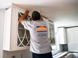 kitchen contractor installing molding with Norfolk logod tee