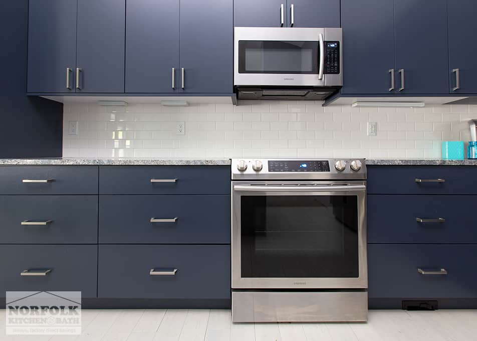 blue kitchen cabinets with kitchen stove and hanging microwave. Colored cabinetry is an up and coming kitchen trend