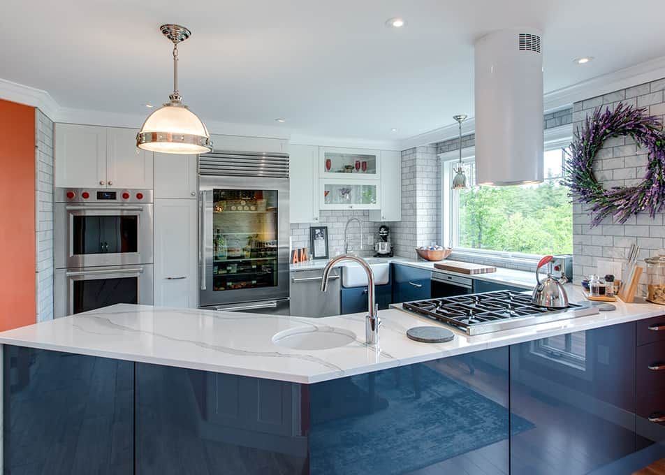 a modern kitchen with blue and white kitchen cabinets, double ovens, a glass refrigerator and countertop range.