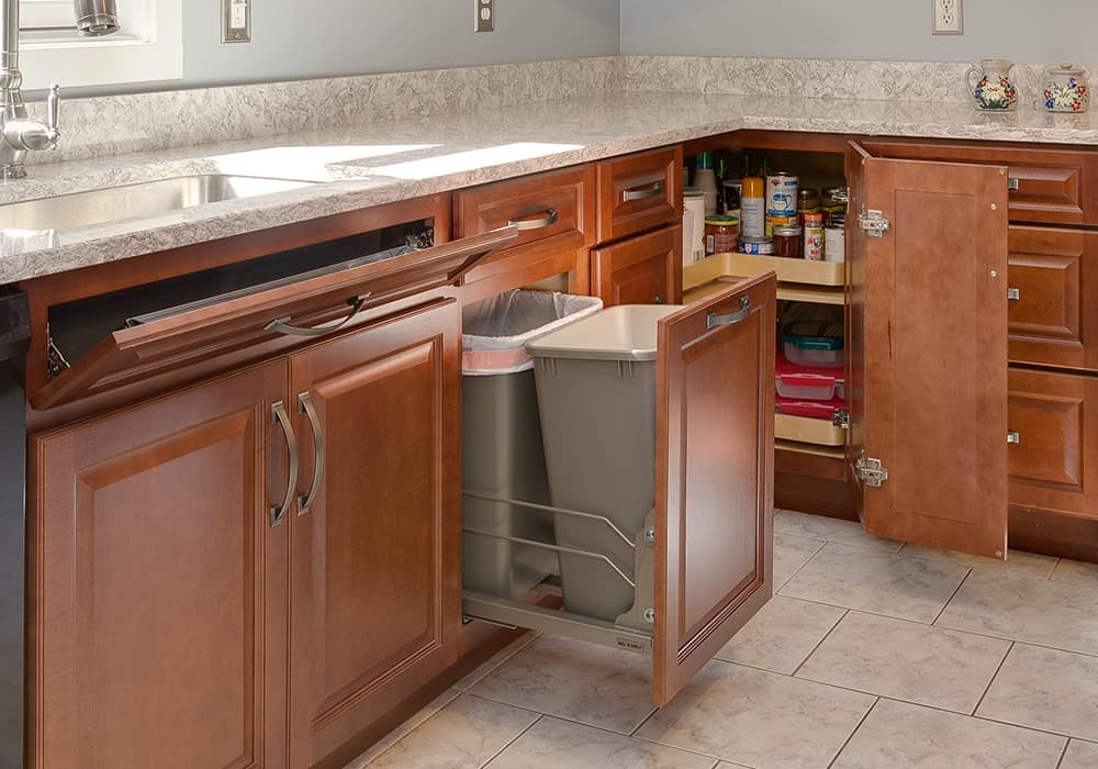 cherry kitchen cabinets with cabinet accessories including a tilt out tray under the sink, a double trash pull out and a lazy susan