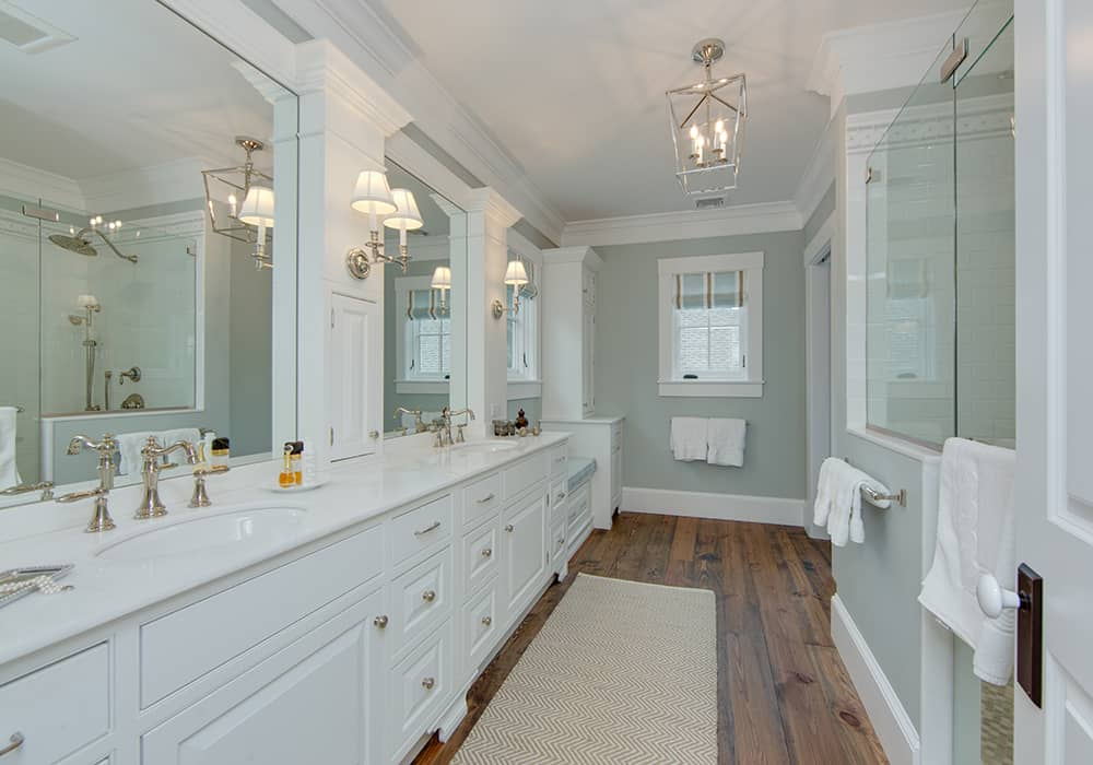 custom bathroom remodel with large white double vanity and a walk in glass enclosed shower and wood flooring