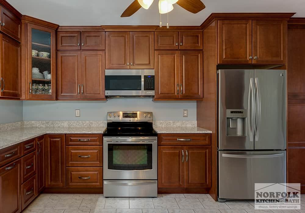 medium tone wood cabinets in kitchen with stainless appliances
