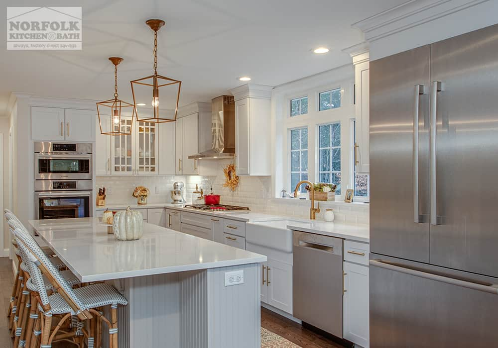 white kitchen with elegant gold finish light fixtures and stainless refrigerator