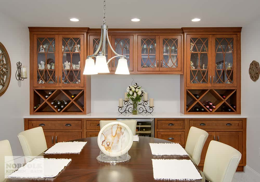 dining table with custom cabinets and wine racks completing a wet bar