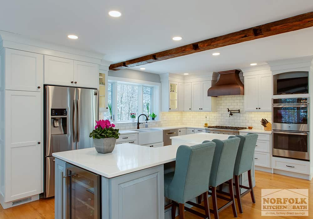 white kitchen with island and wine cooler built in and wood beam accenting above