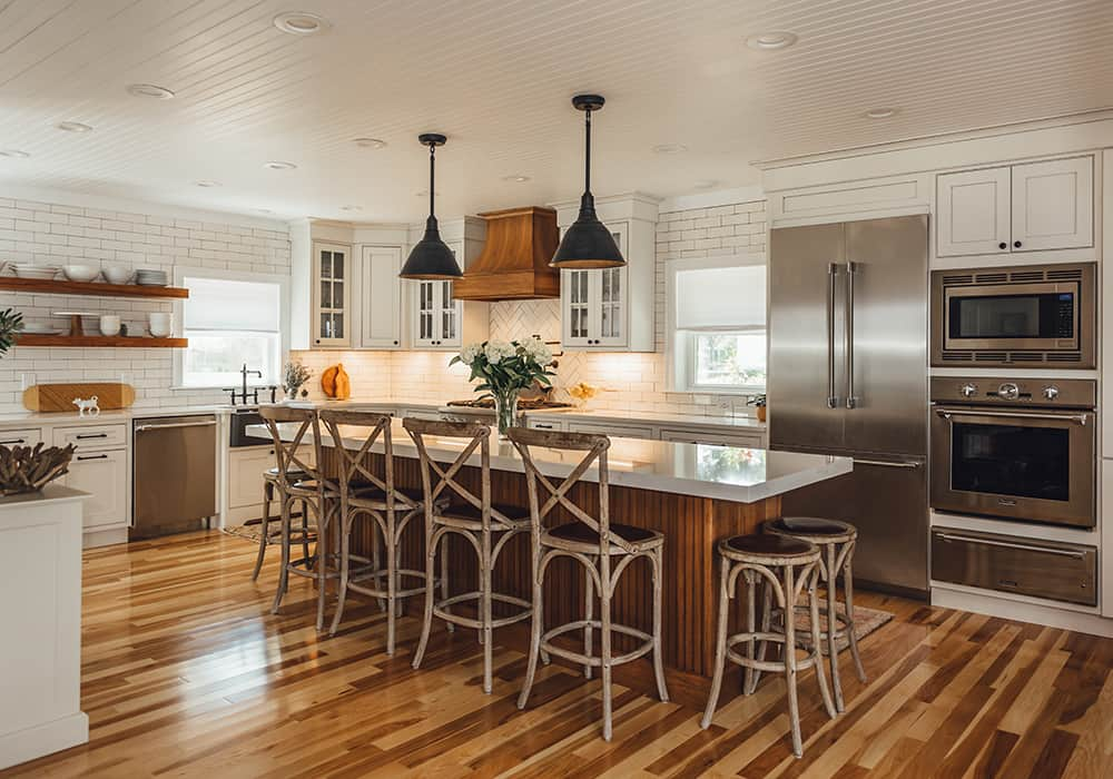 interesting extra large white kitchen with wood color island and stools that look like they were made from tree branches