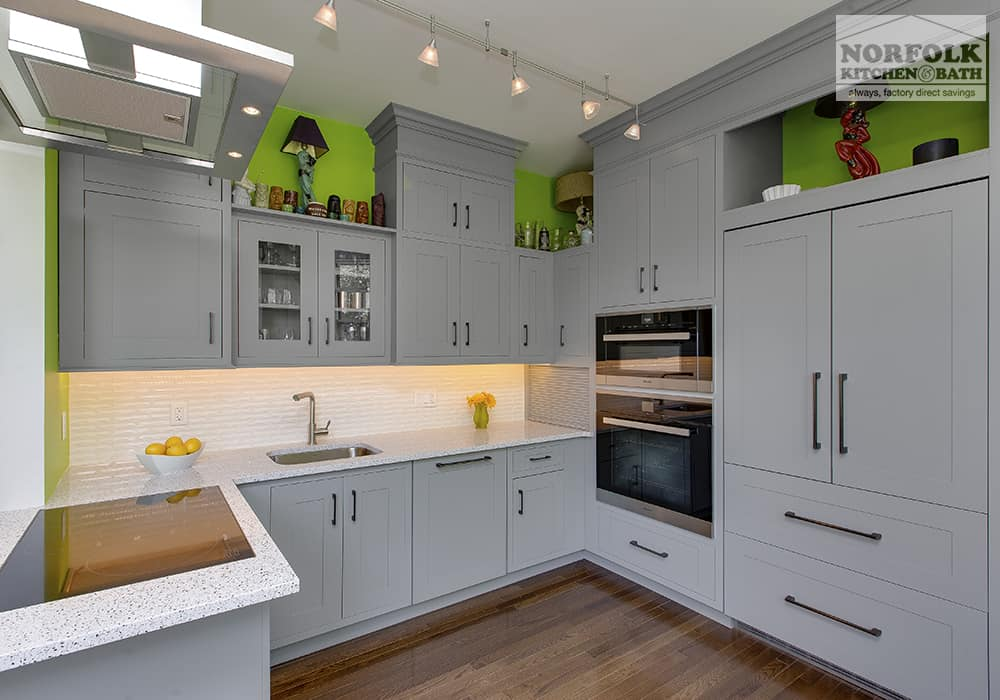 light grey kitchen with bright green paint above wall cabinets and wood floors
