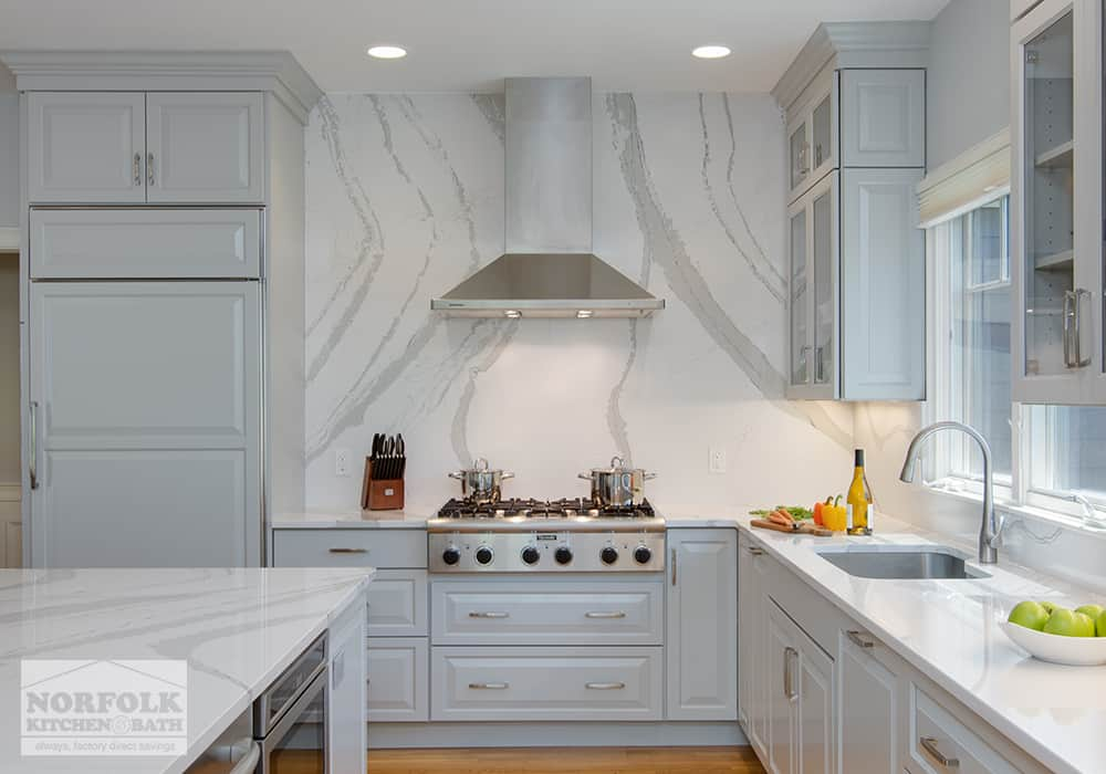 light grey kitchen with head on shot of cook top and stainless hood fan with a marble backdrop