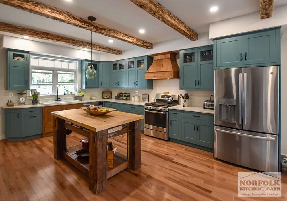 rustic kitchen with green cabinets and wood accents and wood island and wood floors