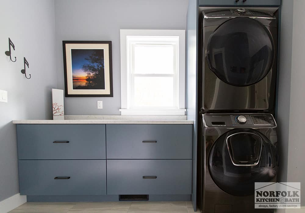 laundry room with blue base cabinets, black hardware and black stainless washer and dryer stacked on each other