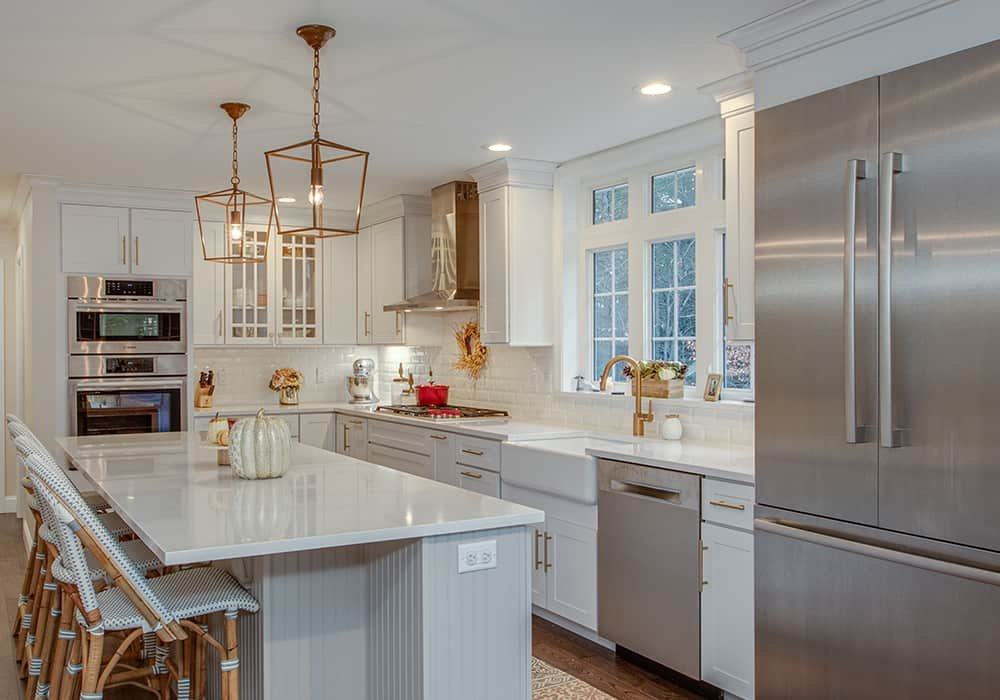 white L-shaped kitchen with a white island, stainless steel countertop and gold pendant lights hanging over the island